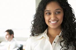 A female co-op student in a workplace smiling